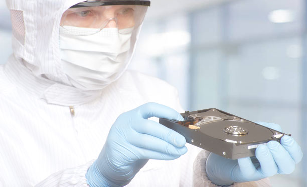 data recovery specialist in cleanroom with hard drive