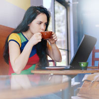 girl drinking coffee over computer